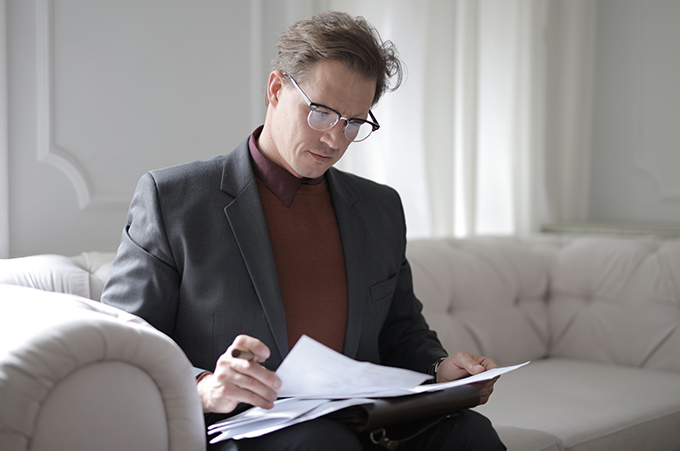 man sitting on a couch in a suit looking at papers